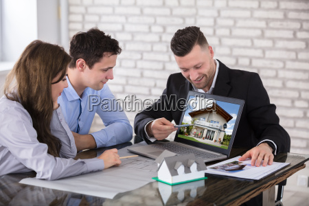 architect showing house model to couple