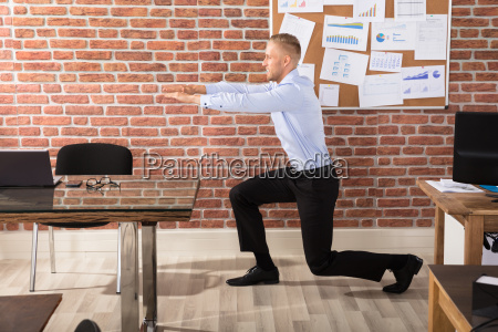 businessman doing exercise in office