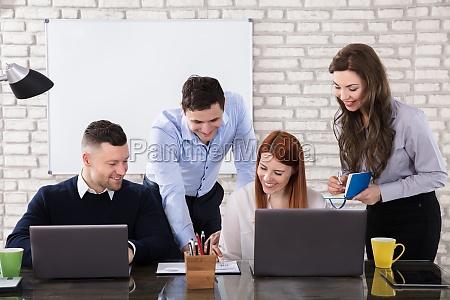 glueckliche geschaeftsleute die am arbeitsplatz arbeiten