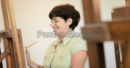 senior woman learning to paint at