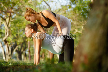 yoga trainer helping pregnant woman with