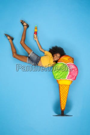 young woman holding onto big icecream