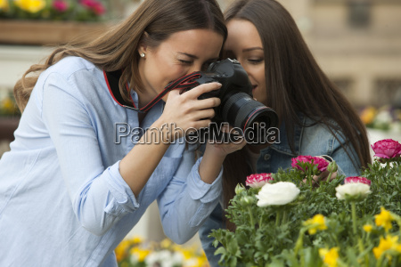 girlfriends photographing potted plants at flower