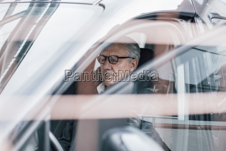 senior businessman sitting in car with
