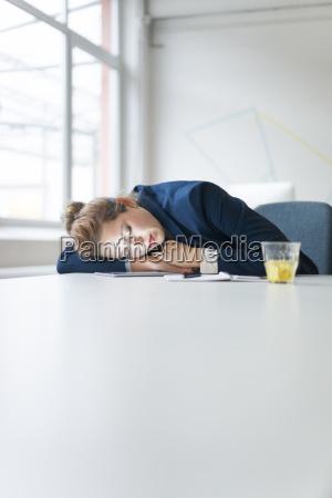 businesswoman fallen asleep over digital tablet