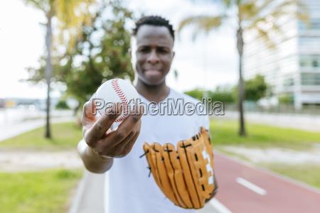 mans hand holding baseball close up