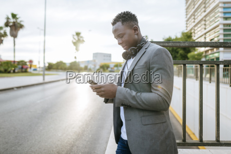 young man standing at roadside looking