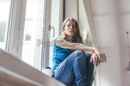 young woman sitting at the window