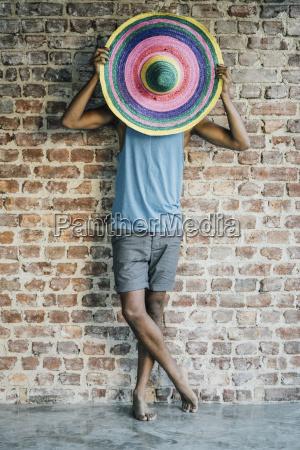 man standing at brick wall covering