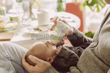 father bottle feeding his newborn baby