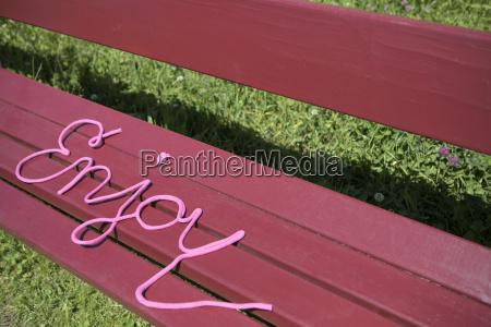 word enjoy on a bench