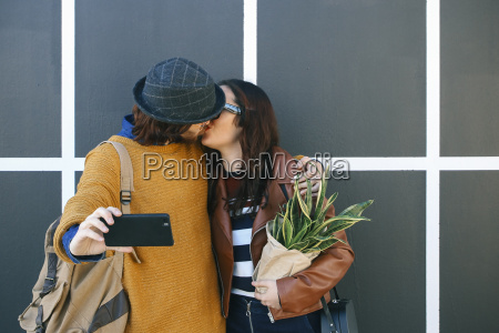 kissing young couple taking selfie with