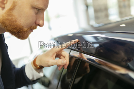 customer touching car paint with his