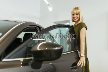 blond woman choosing new car in