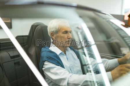 senior man testing convertible in car