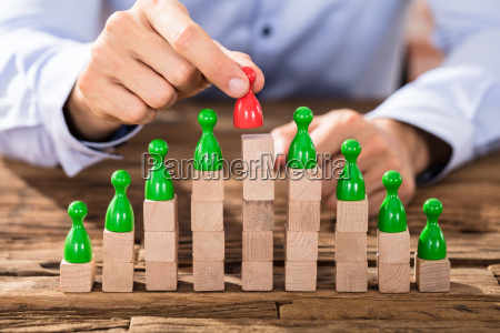 person placing red figure on stacked