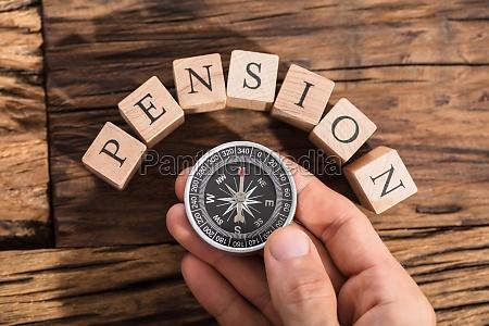 hand haelt kompass auf pension block