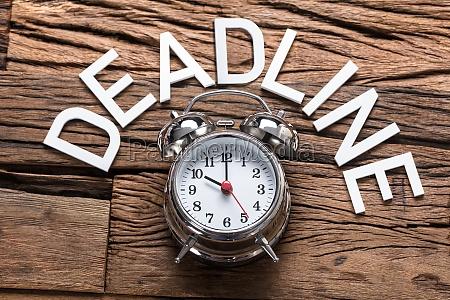 deadline text durch alarmuhr auf holztisch