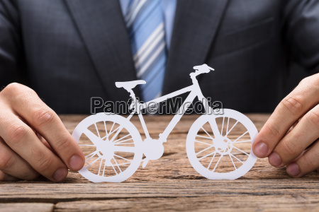 businessman holding paper bicycle at table