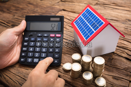 businessman using calculator by coins and