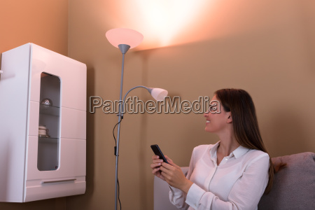 woman controlling electric lamp with mobile