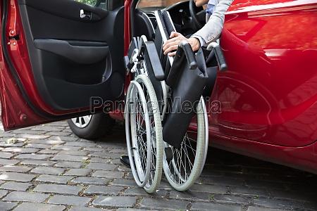 mann der im auto faltet seinen