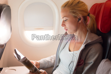 woman reading magazine and listening to