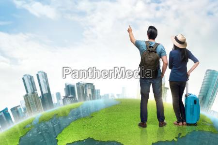 glueckliche asiatische paar touristen mit koffer