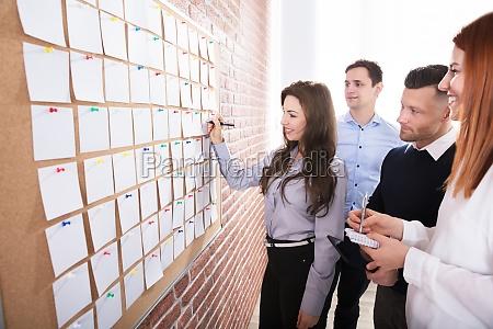 haende die papieranmerkungen ueber corkboard halten