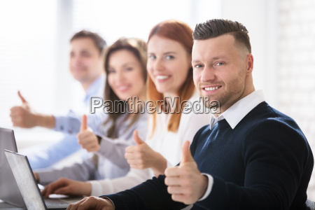 business people showing thumb sign