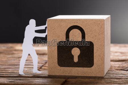 paper man pushing wooden block with