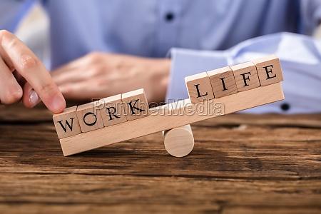 person zeigt misbalance zwischen arbeit und