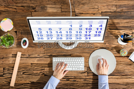 person using computer with calendar on