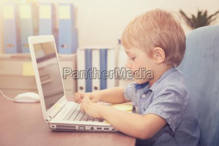 little boy working on the laptop