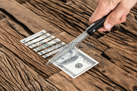 hand cutting the 100 dollar bill
