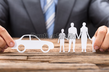 businessman holding paper car and family