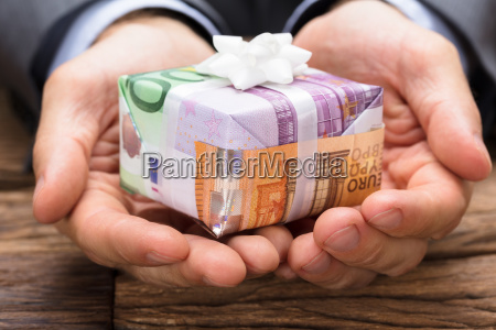 businessman holding gift box made from