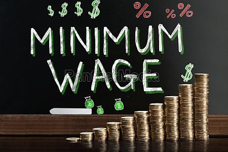 mindestlohn an tafel hinter gestapelten muenzen