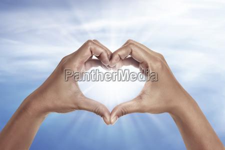 herzfoermige hand mit blauem himmel im