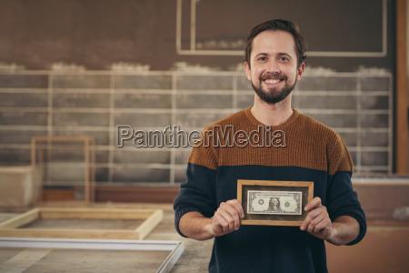 craftsman entrepreneur proudly displaying a framed