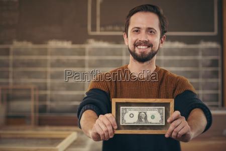 entrepreneur showing framed bank note with