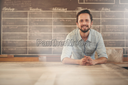 designer leaning on his workbench smiling