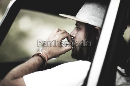 bearded young man wearing baseball cap