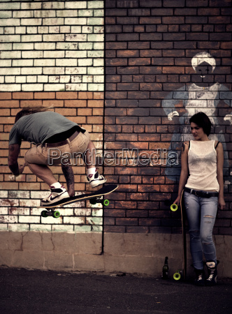 a young man and woman skateboarding