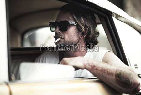 man with moustache sitting in car