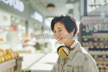 smiling young woman with headphones grocery