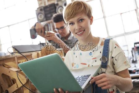 portrait smiling female designer using laptop