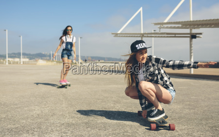 two young women longboarding on beach