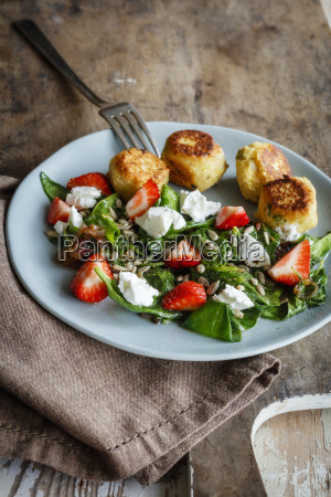 plate of spinach salad with falafel