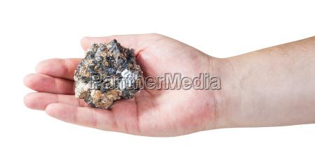 zink und bleimineralerz auf maennlicher handflaeche